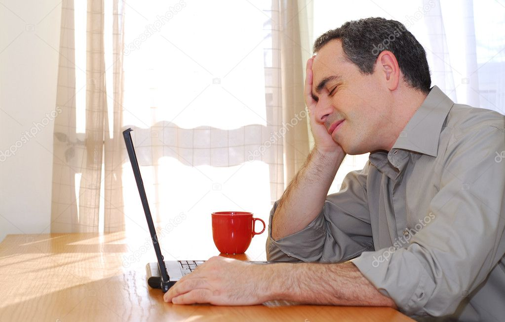 Man sitting at a desk and looking into his computer  Stock Photo #4953800