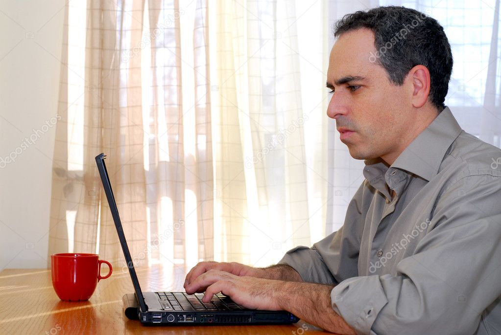 Man sitting at a desk and working on his computer — Stock Photo #4953805