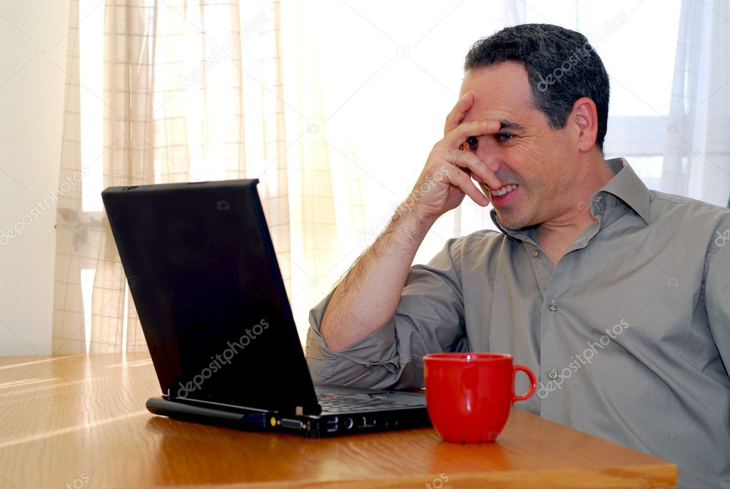 Man sitting at a desk and looking into his computer  Stock Photo #4953807
