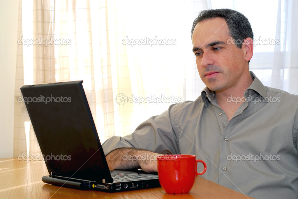 Man sitting at a desk and looking into his computer  Stock Photo #4953819