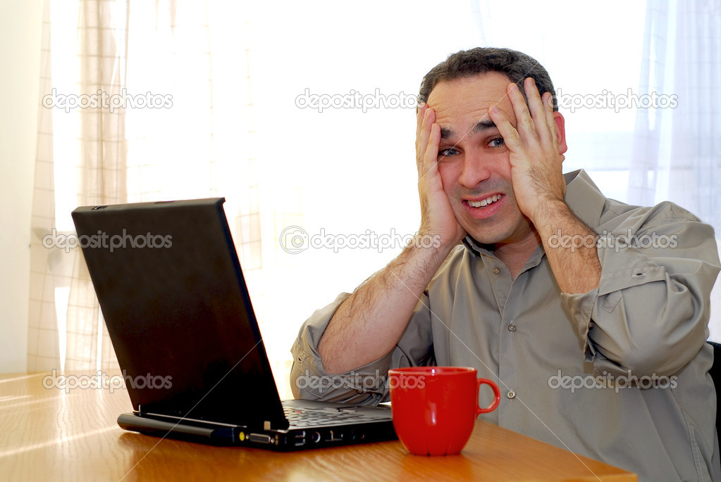 Man sitting at a desk and looking into his computer  Stock Photo #4953822