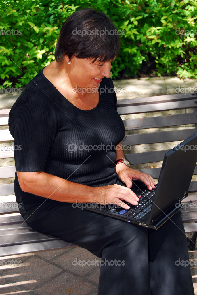 Mature woman typing on portable computer outdoor  Stock Photo #4953952