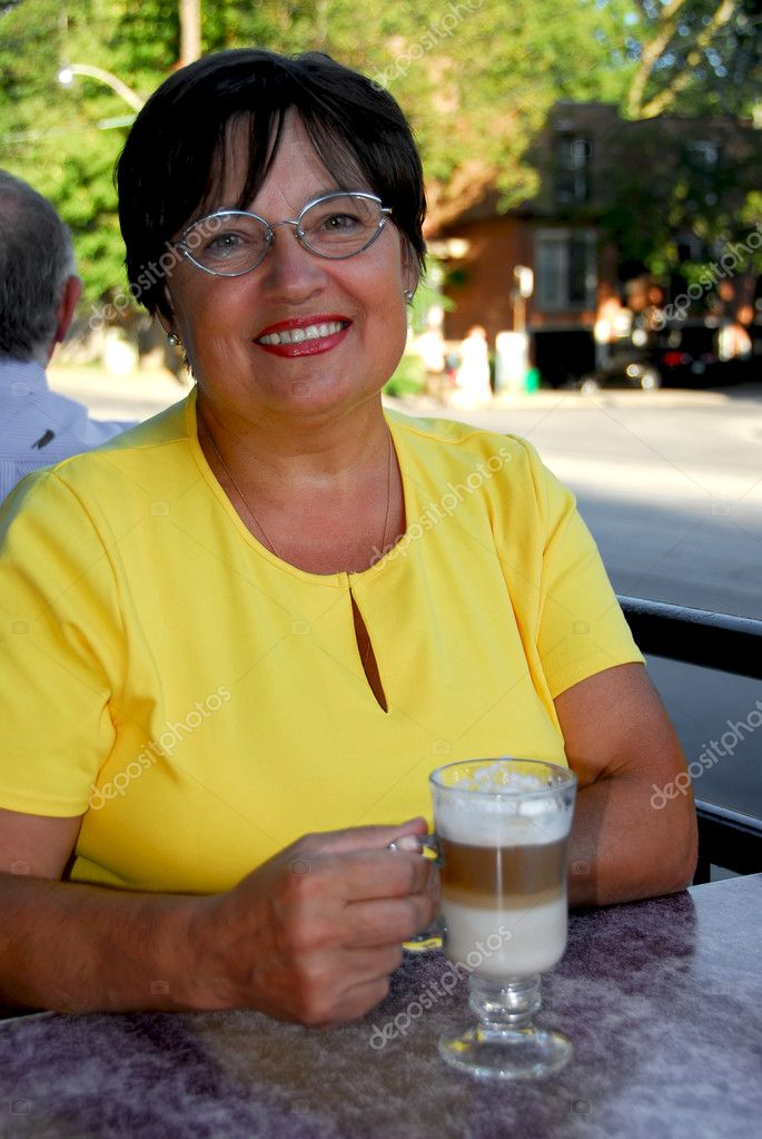 Smiling mature woman in outdoor cafe holding a coffee — Stock Photo #4953960