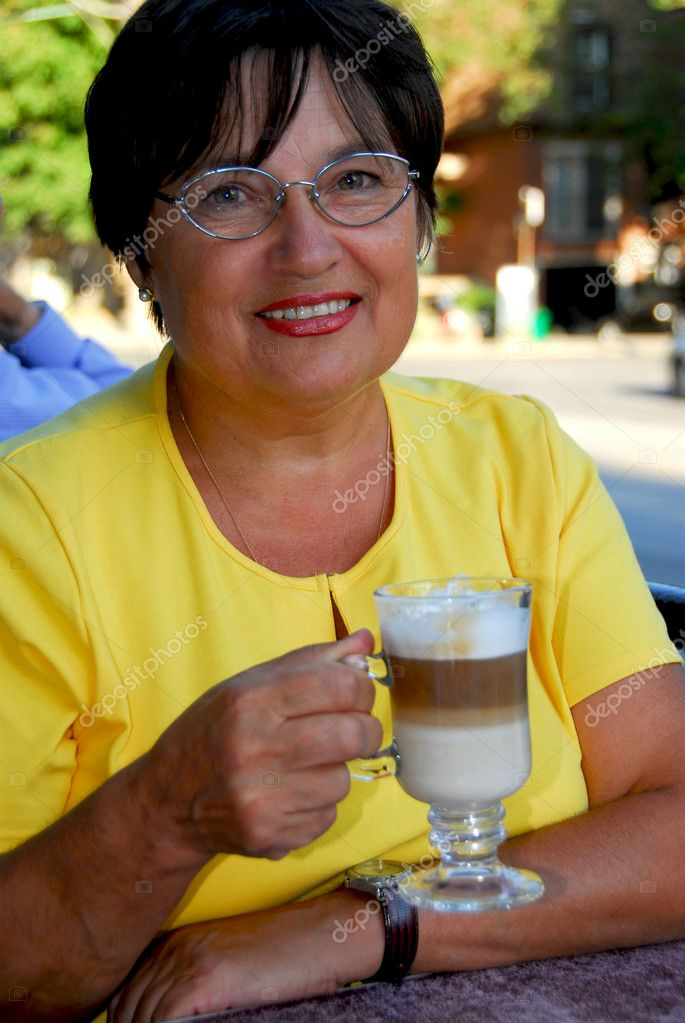 Happy mature woman in outdoor cafe holding a coffee  Stock Photo #4953965