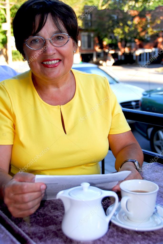 Mature woman reading papers in outdoor cafe  Stock Photo #4954017