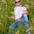 Happy young man in grass — Stock Photo
