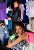 Smiling girl in dress store. She lays on shirts. — Stock Photo