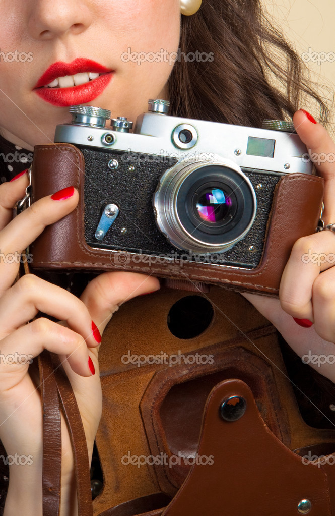 Anonymous closeup young woman holding a old photo camera — Stock Photo #3087118