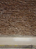 Red brick wall and sidewalk — Stock Photo