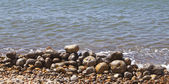 Pebbles stacked up on the edge of the sea — Stock Photo