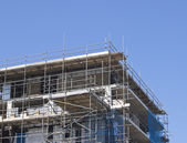 Construction with scaffolding against blue sky — Stock Photo