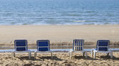 Four blue reclining sun loungers over looking the sea — Stock Photo