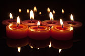 Red candles with flames on a dark background — Stock Photo