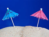 Coctail umbrellas in the sand — Stock Photo
