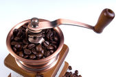 Clouse-up of ancient coffee grinder with coffee grains — Stock Photo