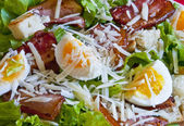Green salad with bacon, eggs and cheese — Stock Photo