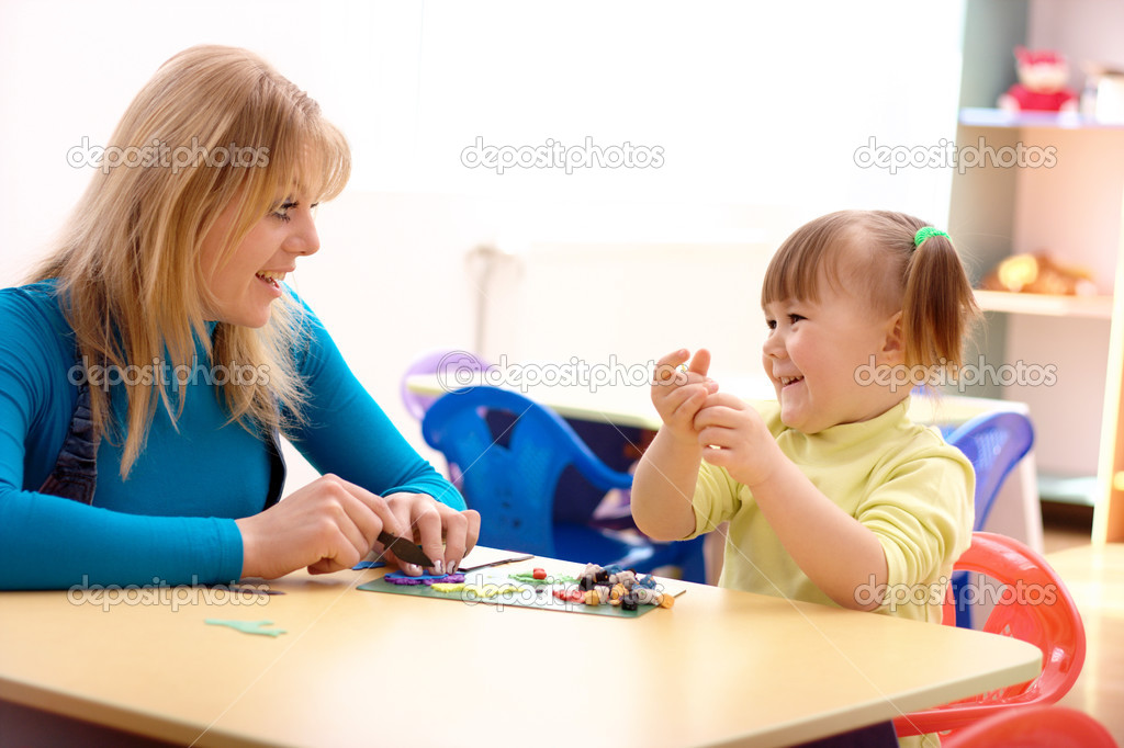 Teacher and cute little girl play with plasticine in preschool — Stock Photo #3066363