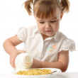 Girl pouring milk in corn flakes — Stock Photo