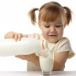 Little girl pouring milk in glass — Stock Photo