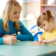 Teacher with child in preschool — Stock Photo
