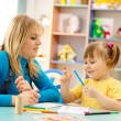 Teacher with child in preschool - Stock Photo