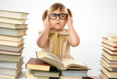 Little girl with books wearing glasses — Stockfoto