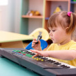 Girl with electronic piano and microphone — Stock Photo