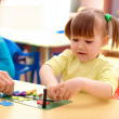 Stock Photo: Teacher and little girl play with plasticine