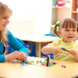 Teacher and little girl play with plasticine — Stock Photo #3257604