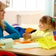 Teacher and little girl play with color paper — Stock Photo #3257605
