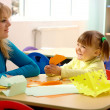 Stock Photo: Teacher and little girl play with color paper