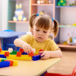 Little girl play with building bricks in preschool — Stock Photo