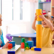 Teacher and preschooler play with building bricks — Stock Photo #3257611