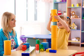 Teacher and preschooler play with building bricks — Stock Photo