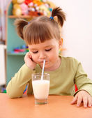 Gloomy little girl drinks milk — Stock Photo