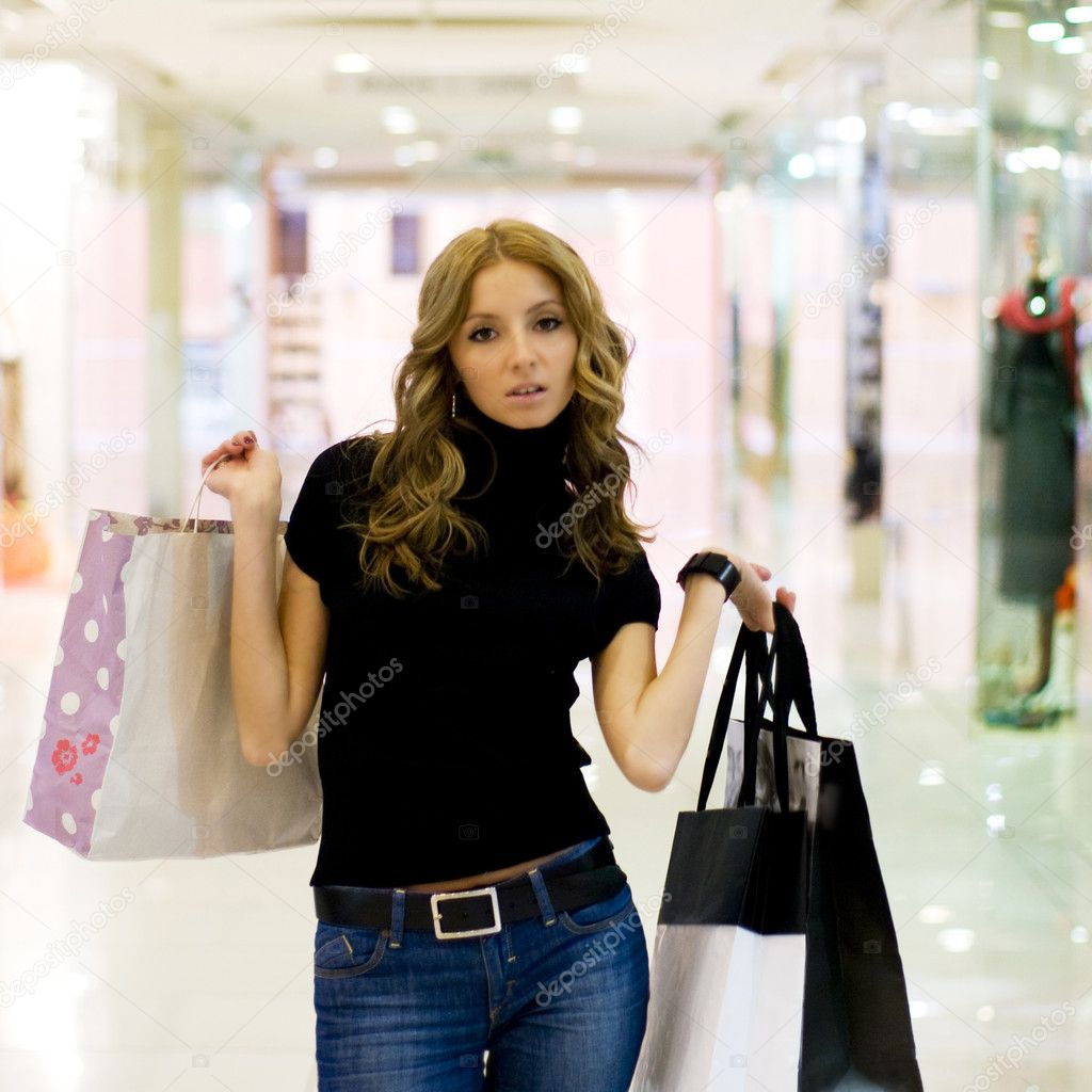 Young caucasian woman walking in shopping center with bags — Stock Photo #3535716
