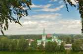 Orthodox church framed by branches under the clouds — Stock Photo