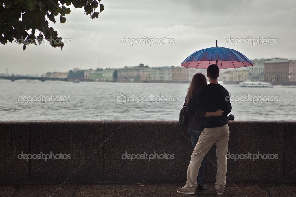 Young pair stay on waterfront under colored umbrella looking at the Saint Petersburg city panorama over river — Stock Photo #3871671
