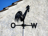 Weather-cock in front of house gable — Stock Photo
