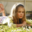 Pretty young girl lying on the grass amo - Stock Photo