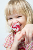 Cute little girl with a heart shape loll — Stock Photo