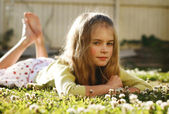 Pretty young girl lying on the grass amo — Stock Photo