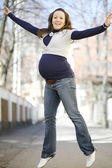 Happy young pregnant woman jumping outdo — Stock Photo