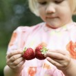 Girl holding two strawberries. — Stock Photo
