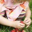 Little girl holding strawberry. — Stock Photo