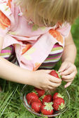 Little girl holding strawberry. — Stock Photo
