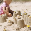 A little girl making sand castles. — Stock Photo