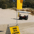Swimming caution sign and flag on beach. — Stock Photo
