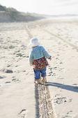 Little girl walking along a tire track o — Stock Photo