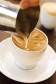 A barista creating latte coffee art. — Stock Photo